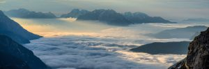view from the top of a mountain looking above clouds and seeing other mountains in the distant